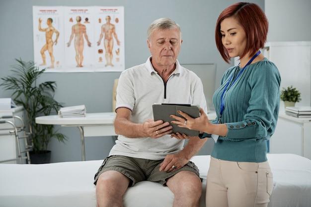Physiotherapeutin spricht mit einem älteren patienten in der arztpraxis und erklärt ihm details der therapie