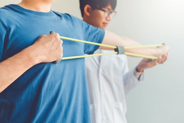 Physiotherapeutmann, der widerstandband-übungsbehandlung über arm und schulter des physiotherapiekonzeptes des männlichen patienten des athleten gibt