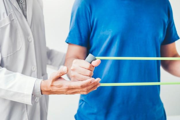 Physiotherapeutmann, der widerstandband-übungsbehandlung über brustmuskeln und schulter des physiotherapiekonzeptes des männlichen patienten des athleten gibt