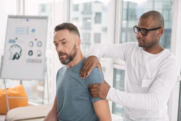 Physiotherapie. schlauer netter mann, der die schulter seines patienten berührt, während die therapie tut
