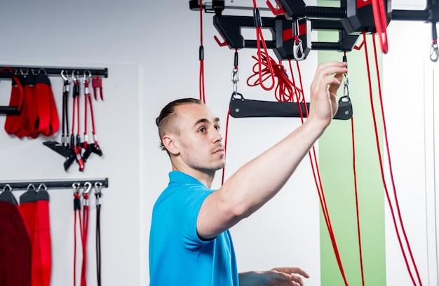 Physiotherapie. suspensionstrainingstherapie. junger mann, der eignungstraktion tut