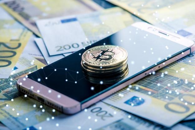 Physische bitcoin-münze auf dem telefonbildschirm auf dem hintergrund von eurobanknoten. kryptowährung und blockchain in unserem leben