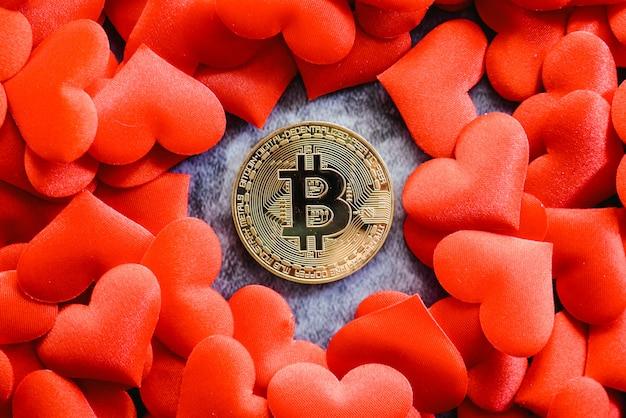 Physische bitcoin-münze auf roten herzen für fans von kryptowährungen.