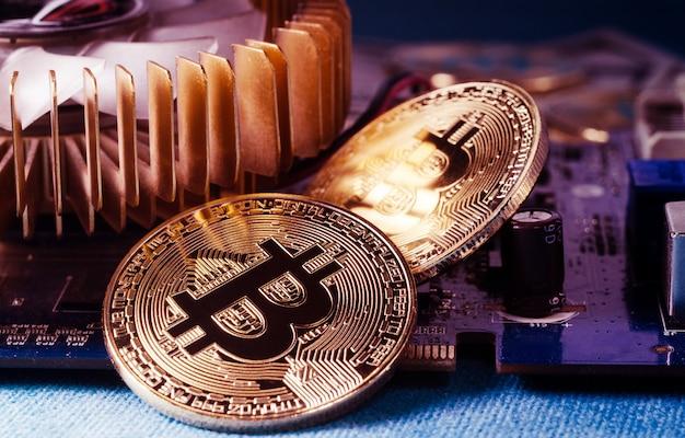 Physische gold-bitcoin-münze auf einer computer-grafikkarte. neue unabhängige weltweite kryptowährung.