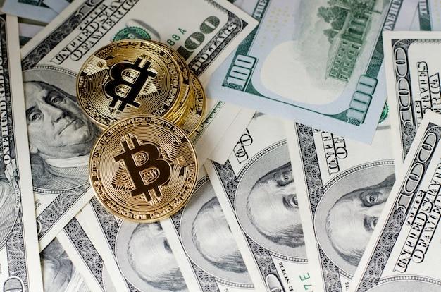 Physische gold-bitcoin-münze gegen dollarscheine und smartphone auf einem purpurroten hintergrund.