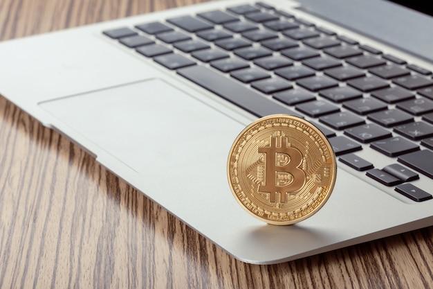 Physisches münzensymbol goldenen bitcoin auf tastatur