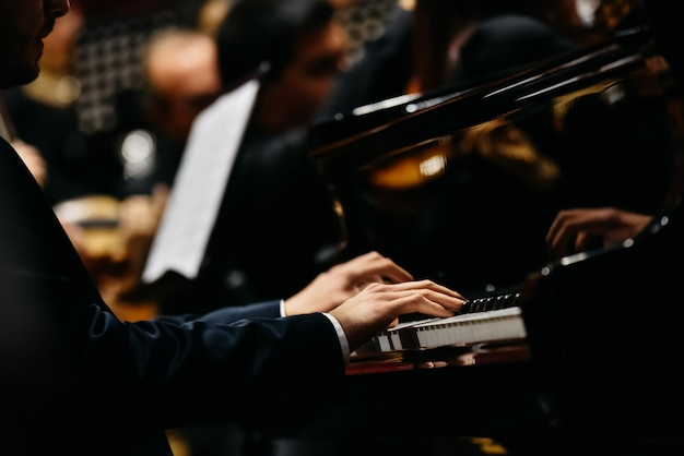Pianist, der ein stück auf einem flügel bei einem konzert spielt, von der seite gesehen.