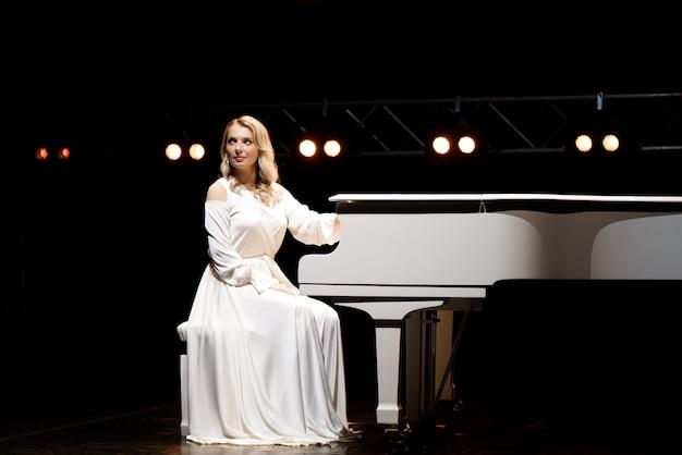 Pianist posiert in der nähe von weißem klavier auf der bühne.