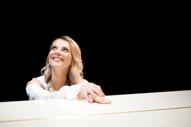 Pianist posiert in der nähe von weißem klavier auf der bühne