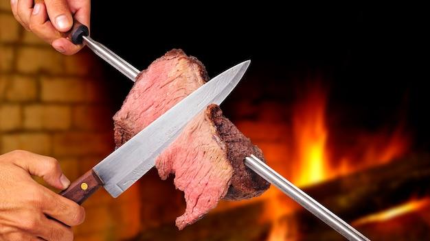 Picanha brasilianisches barbecue über heißen kohlen gebraten messer, das ein stück fleisch am spieß schneidet