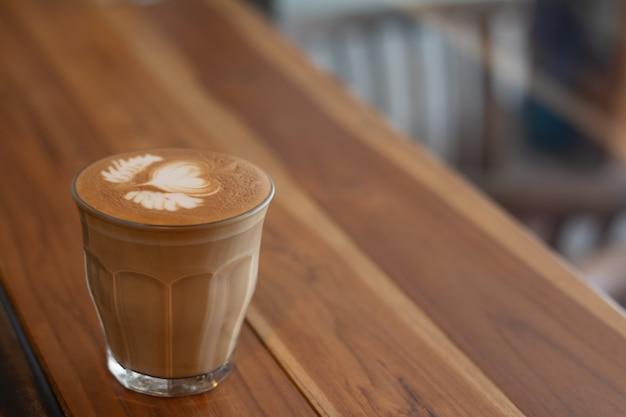 Piccolo latte-kunst im kleinen glas auf hölzernem schreibtisch