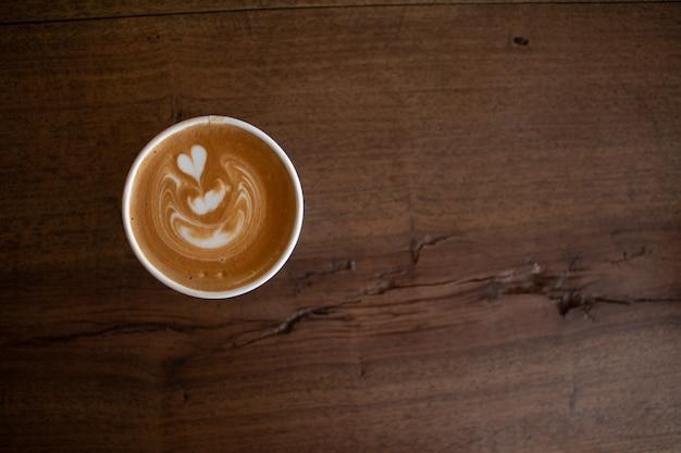 Piccolo latte-kunst in der papierschale auf hölzernem schreibtisch