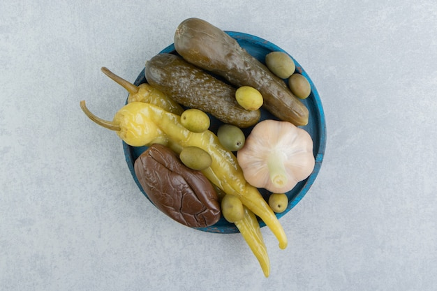 Pickles peperoni, oliven, gurken und auberginen auf der holzplatte auf der marmoroberfläche