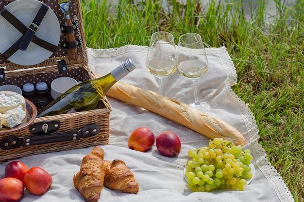 Picknick am see: tischdecke, picknickkorb mit geschirr