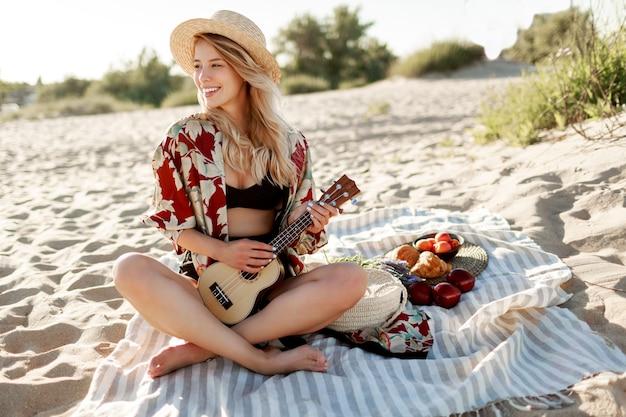 Picknick auf dem land. frau im strohhut sitzt auf abdeckung am strand in den sanften farben des sonnenuntergangs und spielt ukulelegitarre. frisches obst, croissants und pfirsich auf dem teller.