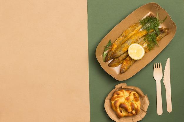 Picknick-essen in umweltfreundlichem einweggeschirr aus pappe. brauner und grüner hintergrund. speicherplatz kopieren. flach liegen