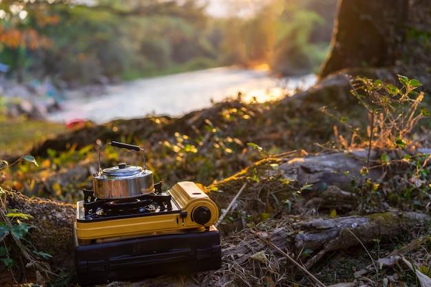 Picknick-gasherd und aluminium-teekanne zum kochen von wasser beim camping