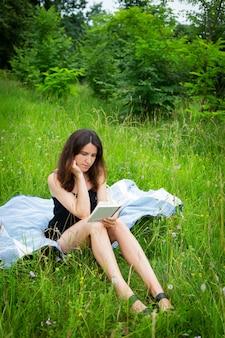 Picknick im freien. ein mädchen liest ein buch im freien, während es auf einem blauen plaid sitzt. das mädchen genießt die frische luft. erholung im freien, nahaufnahme.