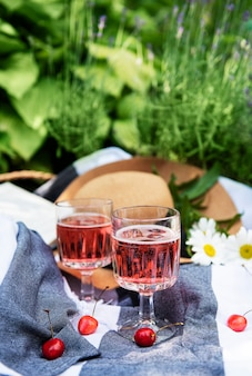 Picknick im freien in lavendelfeldern. roséwein im glas, kirschen und strohhut auf decke