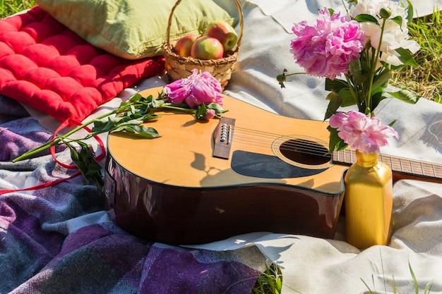 Picknick im freien mit gitarre, äpfeln, kissen und pfingstrosen