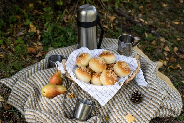 Picknick im freien. thermoskanne mit tee kaffee, leckere brötchen