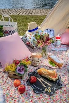 Picknick im park. sandwiches, äpfel und blumen.