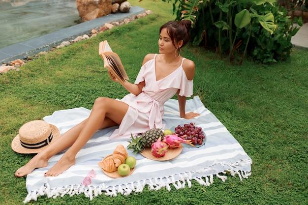 Picknick im tropischen garten. romantische asiatische frau im rosa kleid, das auf abdeckung sitzt und buch liest.
