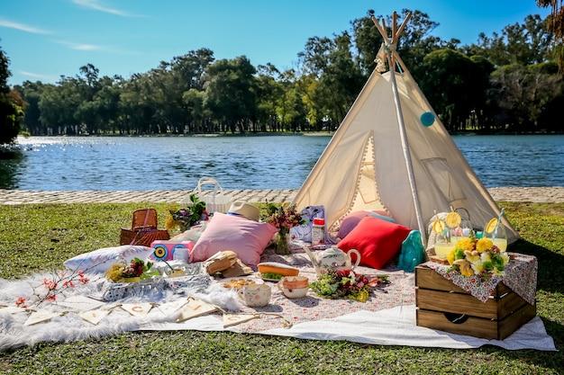Picknick in decke und zelt im park mit dem see.
