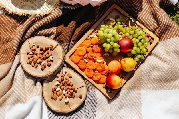 Picknick in der natur. auf dem plaid sind frische früchte, trockenfrüchte und nüsse auf einem tablett angeordnet.