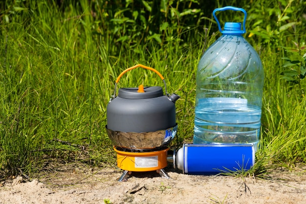 Picknick in der natur. ein gasbrenner und eine tasse heißen tee.