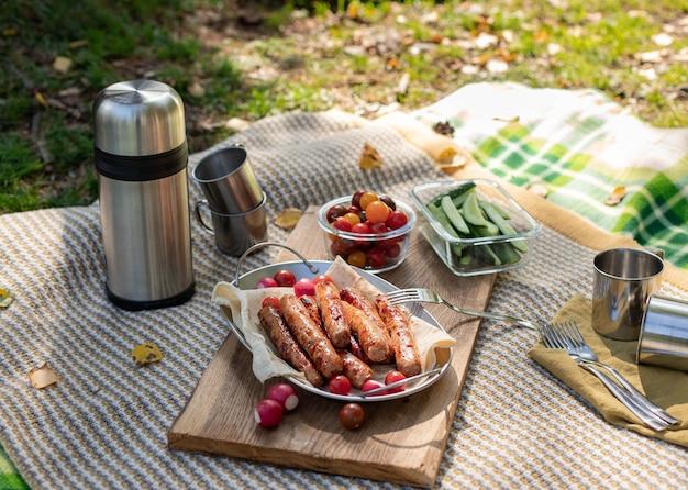 Picknick in der natur, sonniger tag im wald. gegrillte würstchen mit frischem gemüse