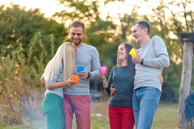 Picknick mit freunden am feuer. firmenfreunde beim picknick. freunde erzählen geschichten. sommerpicknick. hab spaß mit freunden