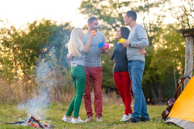 Picknick mit freunden am feuer. firmenfreunde, die einen wanderungspicknick-naturhintergrund haben. freunde erzählen geschichten. sommerpicknick. hab spaß mit freunden