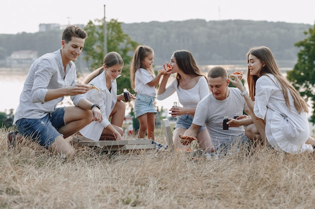 Picknickfreunde mit pizza und getränken, sonnigem tag, sonnenuntergang, gesellschaft, spaß, paaren und mutter mit baby