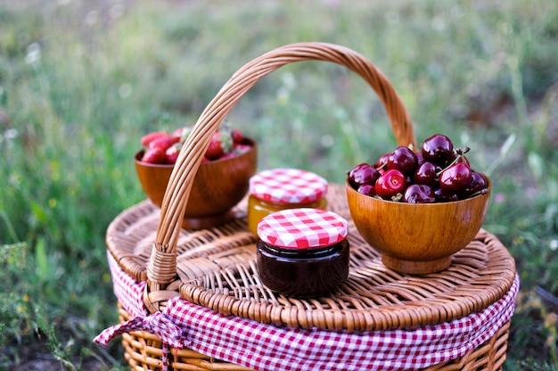 Picknickkorb auf dem feld mit marmelade und kirschen