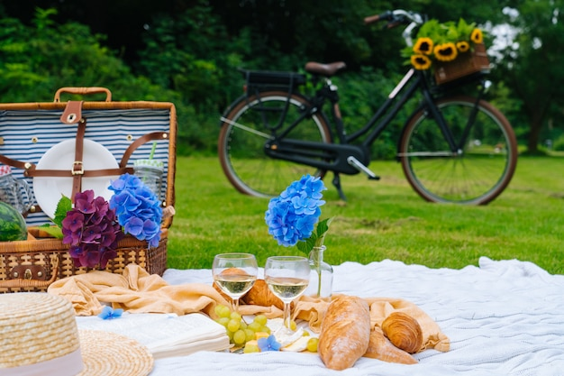 Picknickkorb auf gras mit essen und trinken auf strickdecke. fahrrad auf hintergrund. selektiver fokus.