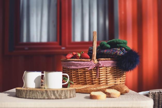 Picknickkorb mit erdbeeren und wollmützen an einem sonnigen tag