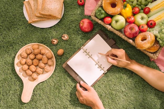 Picknickkorb mit essen, brot, obst und orangensaft auf einem rot-weiß karierten tuch auf dem feld mit grünem naturhintergrund. picknick-konzept.