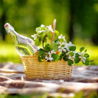 Picknickkorb mit früchten, blumen und wasser in der glasflasche