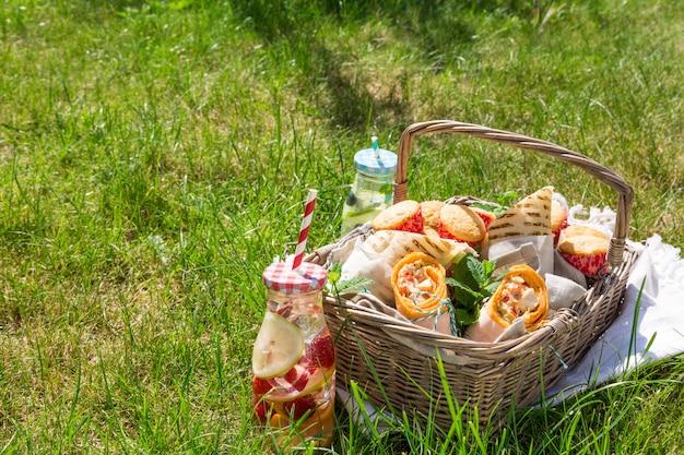 Picknickkorb mit lebensmittel auf grünem sonnigem rasen