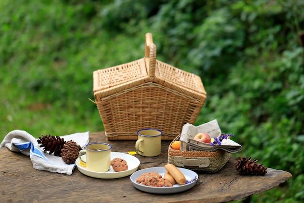 Picknickkorb mit obst und backwaren auf altem rustikalem holztisch mit grüner landschaft