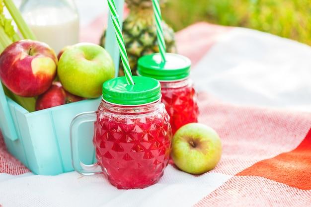 Picknickkorb, obst, saft in kleinen flaschen, äpfel, ananas sommer, ruhe, plaid, gras copyspace