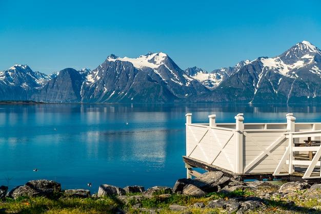 Picknickplatz raststätte holztisch dekoration und norwegische flagge am see fjord ufer.