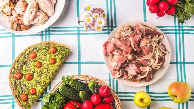 Picknicktisch mit rohem mariniertem fleisch, gemüse und kuchen. sommerzeit.