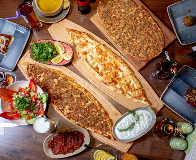 Pide und lahmajun serviert mit salat, gemüse und zitrone, linsensuppe und ayran