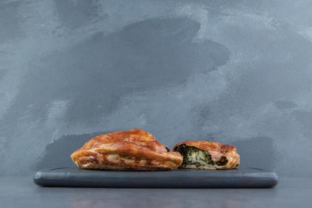 Pie gefüllt mit grüns auf schwarzem schneidebrett.