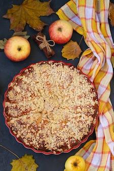 Pie mit äpfeln befindet sich in keramikform auf dunklem hintergrund, draufsicht, nahaufnahme, vertikale ausrichtung