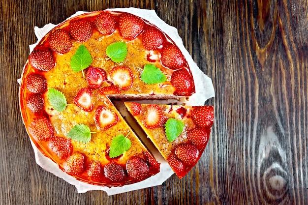 Pie mit erdbeere, kissel, gelee und minze auf pergamenthintergrund auf holzbrett oben