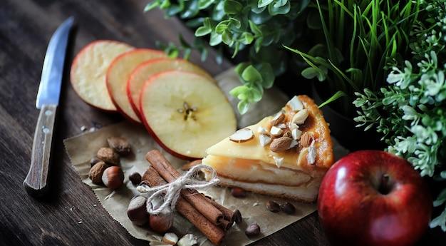 Pie mit zimt und äpfeln auf einem holztisch. frisches gebäck mit zimtstangen mit walnüssen und zuckerpulver. brötchen mit nüssen und zimt auf dem tisch.