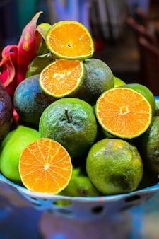 Piel von asiatischen exotischen früchten auf der platte. äpfel, orangen, mangos, drachen und maracuja.